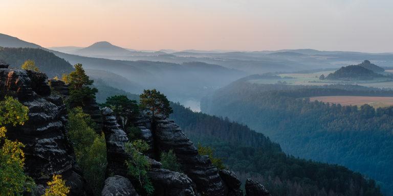 Leinwandbild - Morgendliche Felsen an der Elbe im Nebel