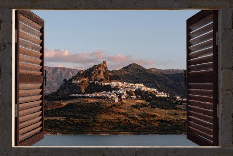Leinwandbild - Fensterblick auf das Bergdorf Zahara de la Sierra in Andalusien bei Sonnenuntergang