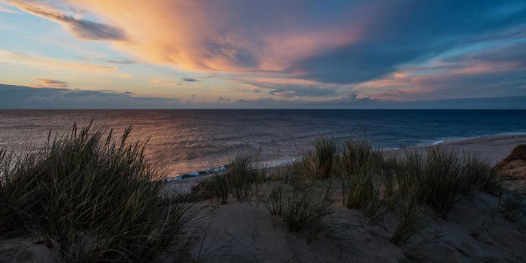 Leinwandbild - Leuchtende Abendwolken am Meer